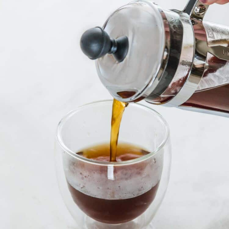Pouring coffee from a french press into a double glass cup