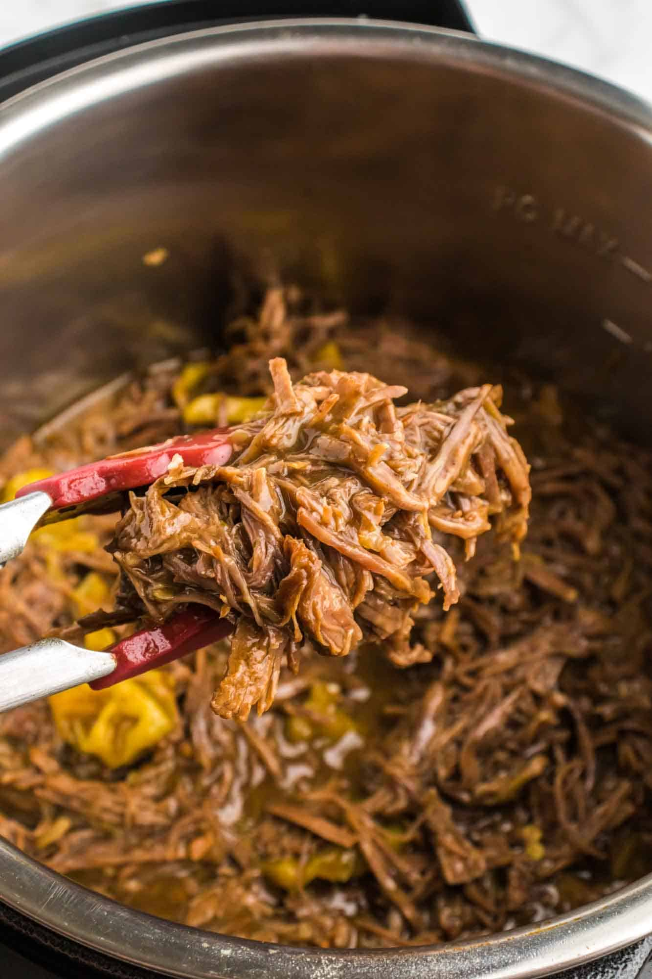 Taking shredded beef out of the Instant Pot using kitchen tongs
