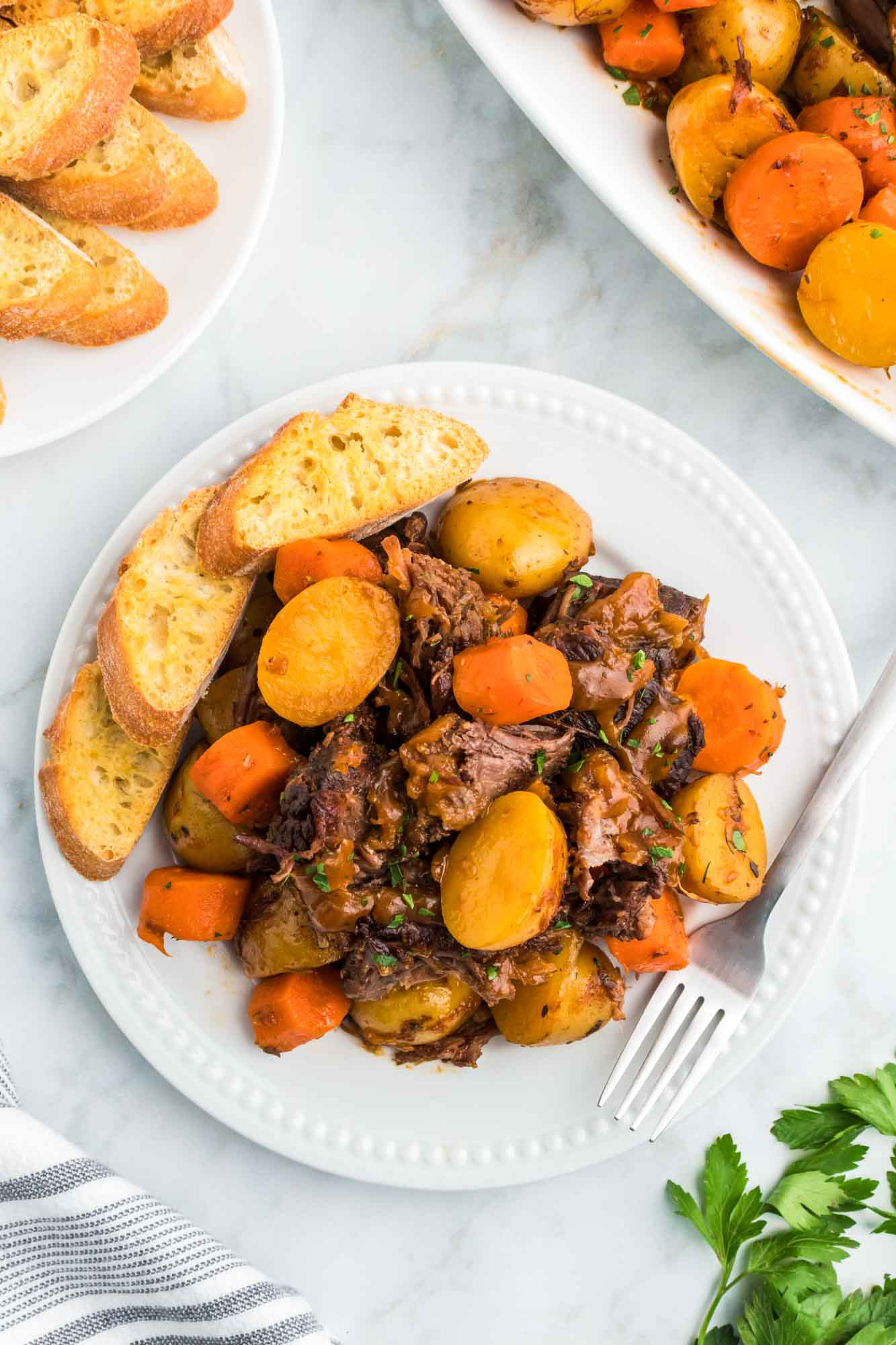 Pot roast served in a white plate with garlic bread on the side