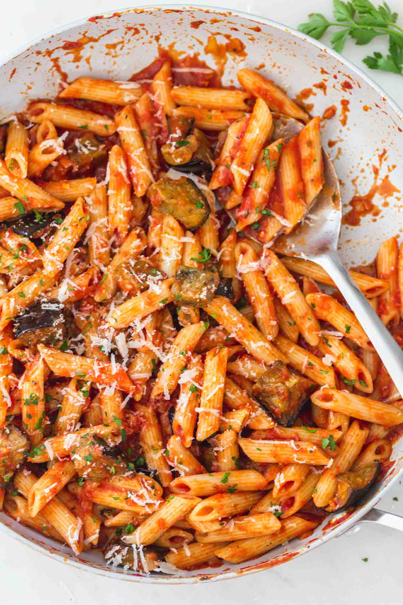eggplant pasta in a large skillet with a serving spoon