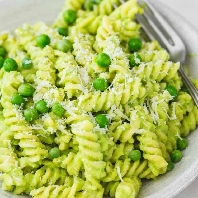Green pasta with peas in a bowl and fresh peas