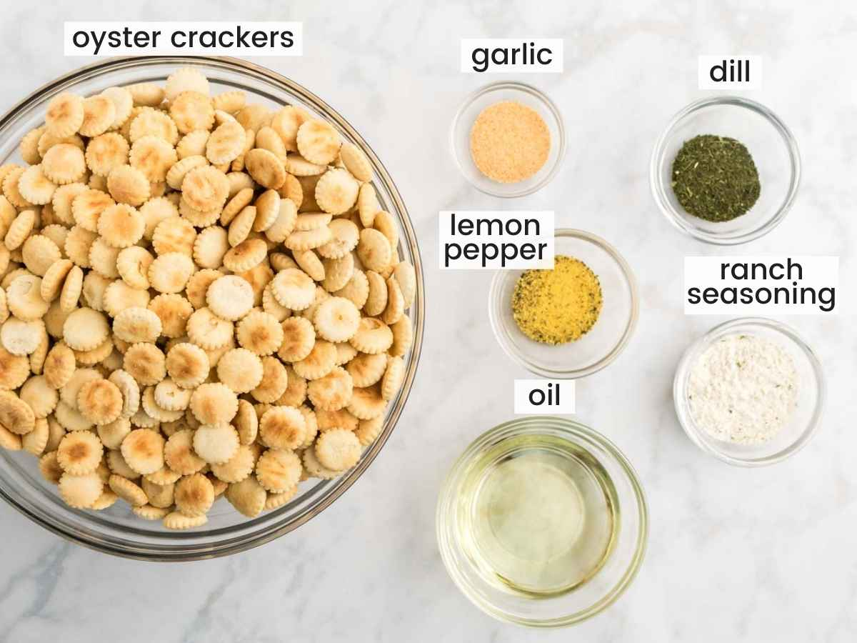 Ingredients needed to make ranch oyster crackers including ranch seasoning, oyster crackers, lemon pepper, garlic, dill, and oil.