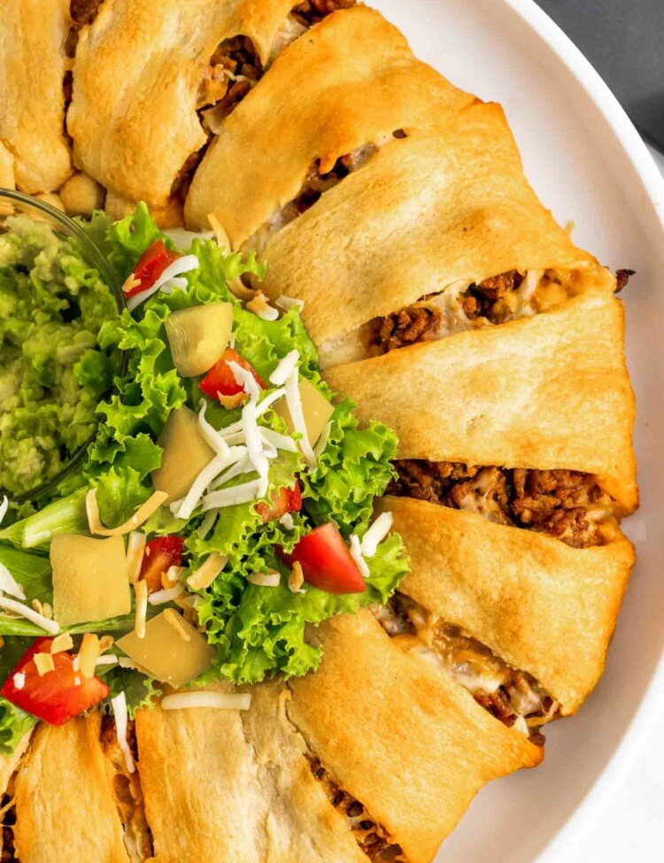 Overhead shot of a taco ring served with salad and guacamole in the middle