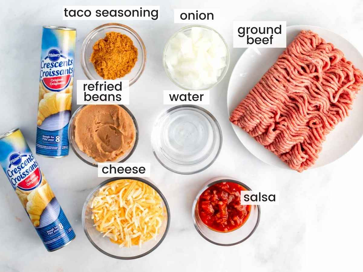 Ingredients needed to make taco ring including ground beef, crescent rolls, salsa, refried beans, onion, and cheese.