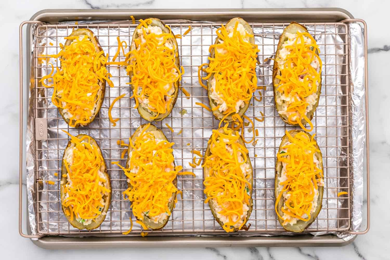 Twice baked potatoes topped with cheese, placed on a wire rack