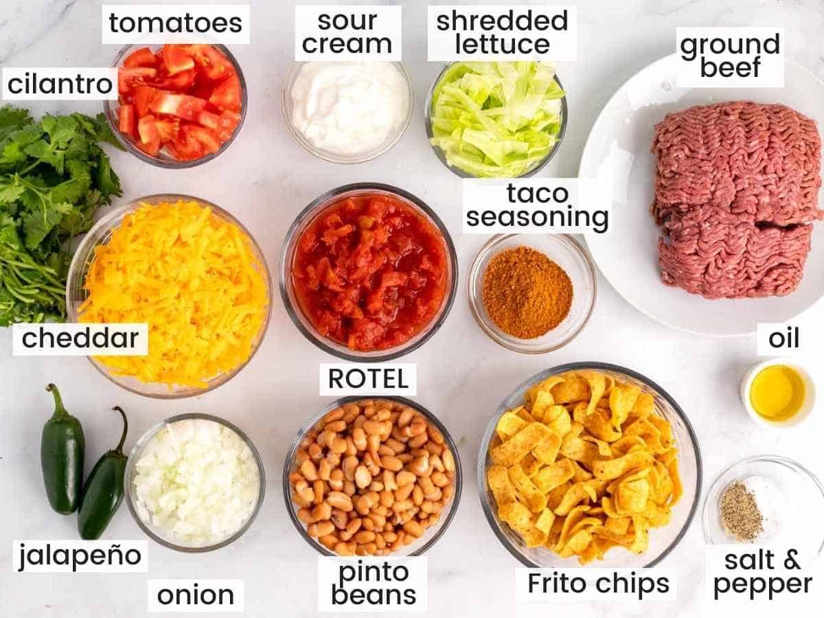 Ingredients needed to make a walking taco casserole including ground beef, cheese, frito chips, pinto beans, lettuce, seasonings and aromatics.