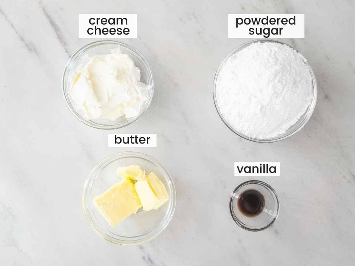 Ingredients needed to make cream cheese frosting including butter, powdered sugar, cream cheese, and vanilla extract.