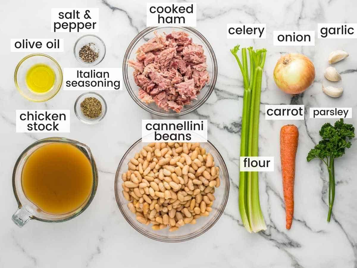 ingredients needed to make ham and bean soup including cooked ham, beans, aromatics, stock, and seasonings.