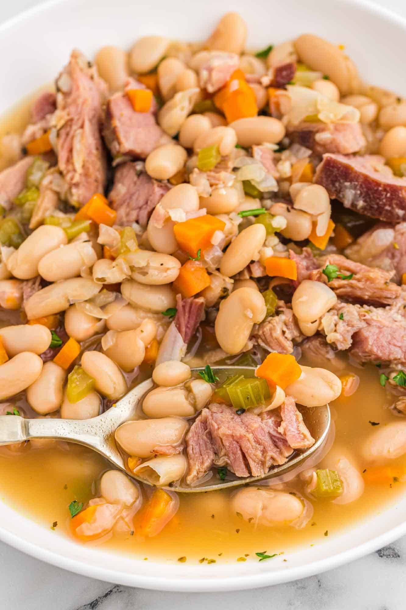 Ham and bean soup served in a white bowl with a spoon.