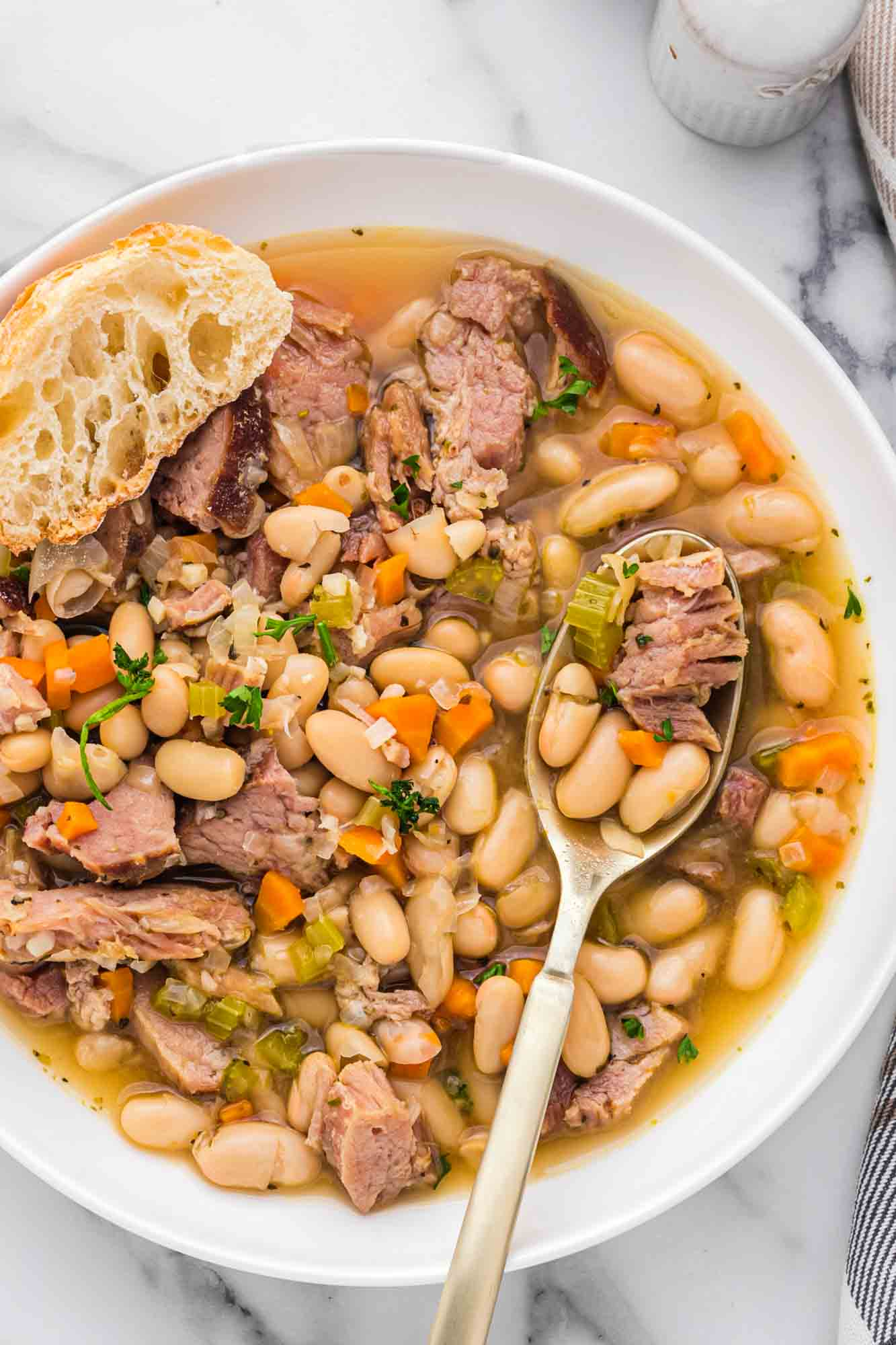Overhead shot of ham and bean soup served in a white bowl with crusty bread on the side, and a spoon.