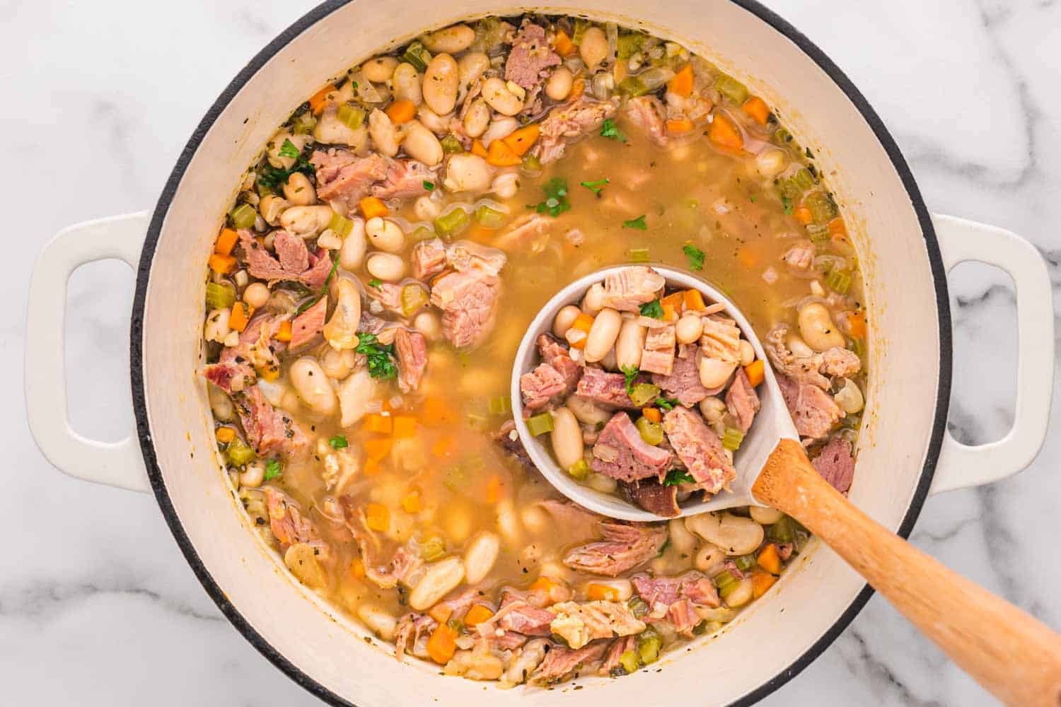 Ham and bean soup in a white dutch oven with a soup ladle
