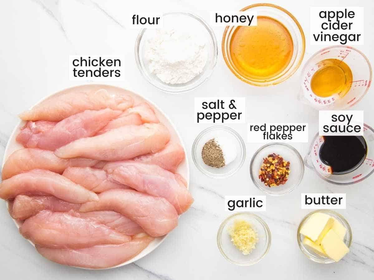 Ingredients needed to make honey garlic chicken tenders including chicken tenders, honey, garlic, soy sauce, garlic, butter, red pepper flakes, flour.