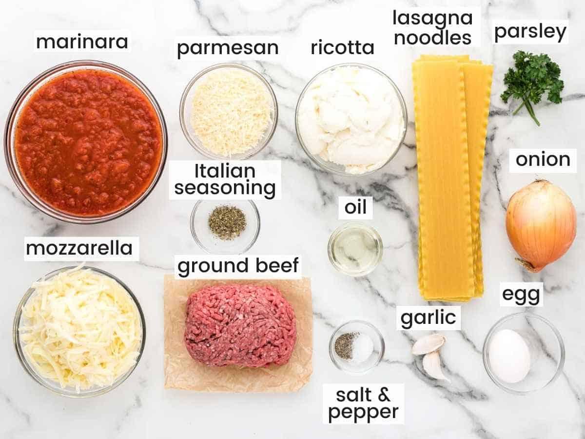 Ingredients needed for making lasagna roll ups, including ground beef, marinara, parmesan, mozzarella, ricotta, lasagna noodles, onion, egg, garlic, oil, salt and pepper.