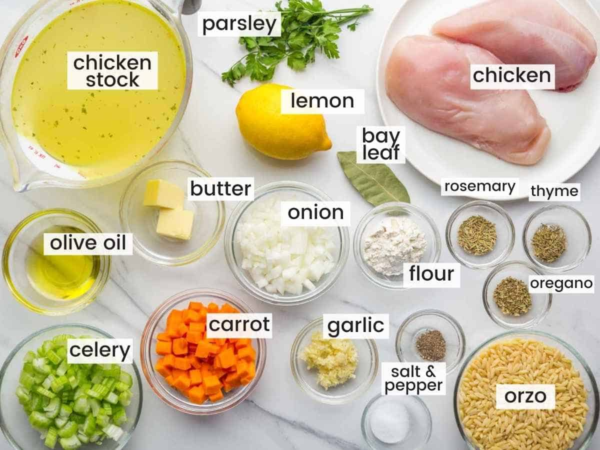 Ingredients needed to make lemon chicken orzo soup including chicken breasts, broth, carrots, celery, onion, garlic, lemon, and seasonings.