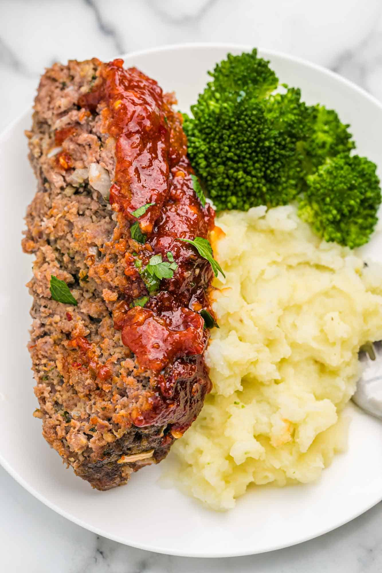 Slice of meatloaf served on a white plate with mashed potatoes and steamed broccoli