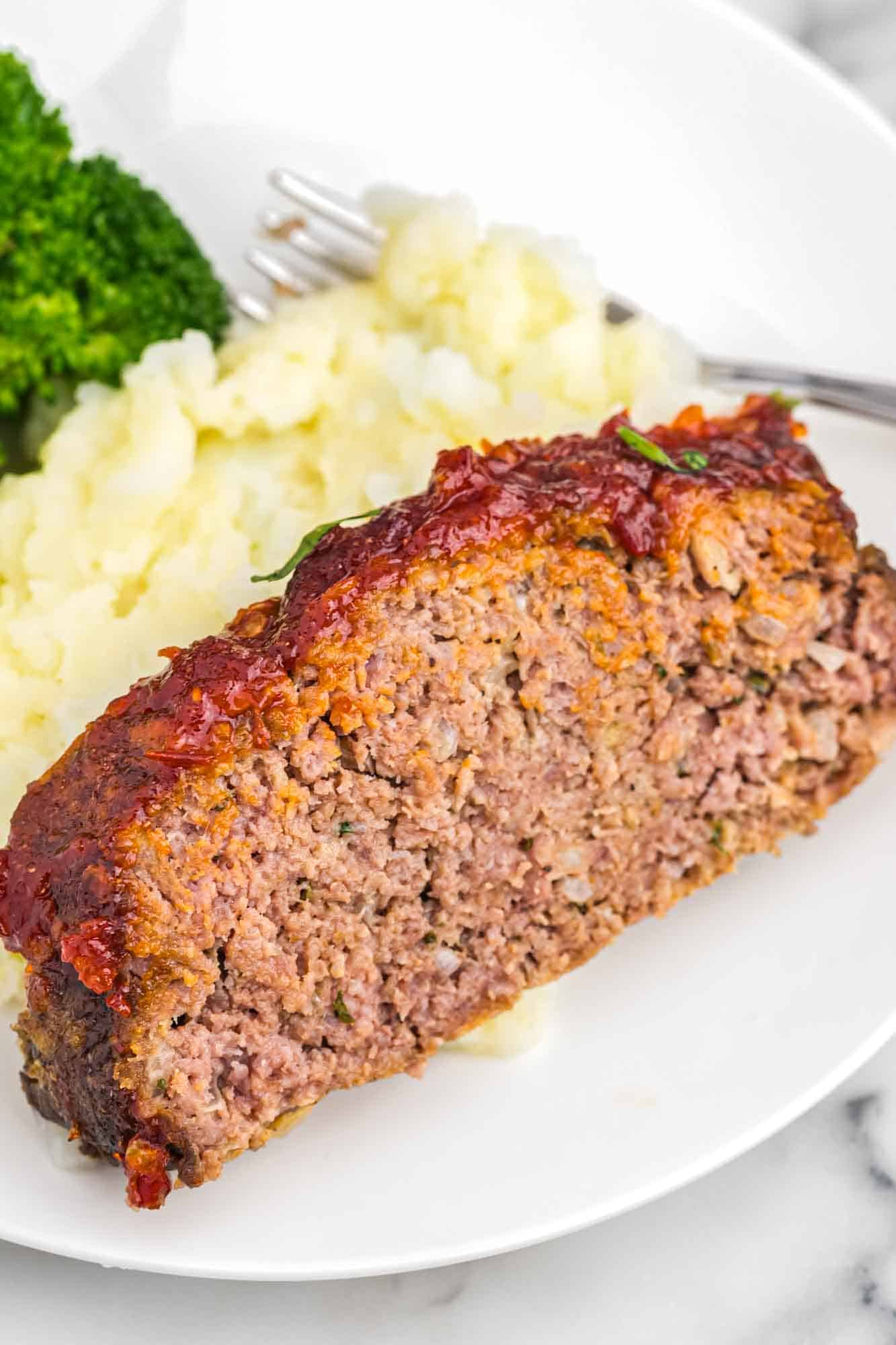 A slice of meatload served with mashed potatoes and steamed broccoli