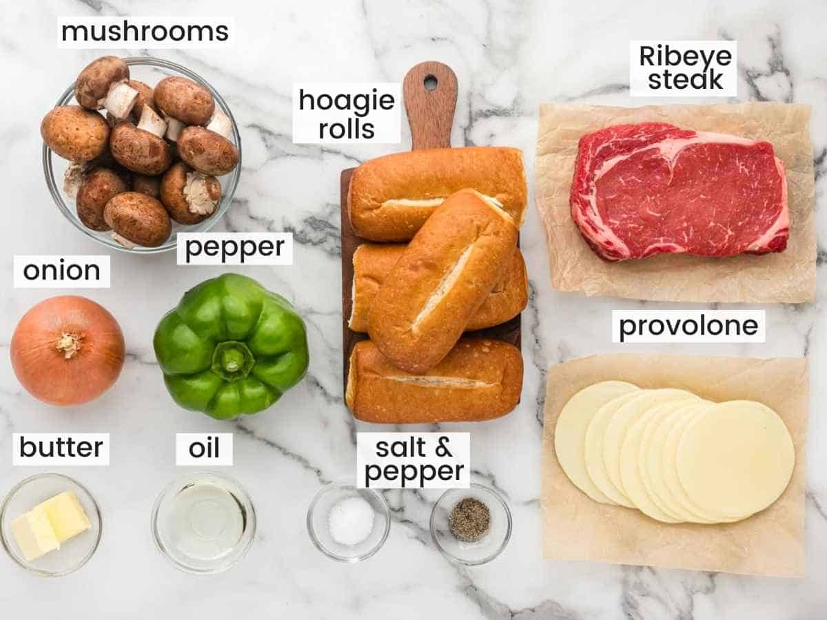 Ingredients needed for Philly cheesesteak sandwiches including steak, hoagie rolls, provolone cheese, mushrooms, bell peppers, onion, butter, oil, salt and pepper.