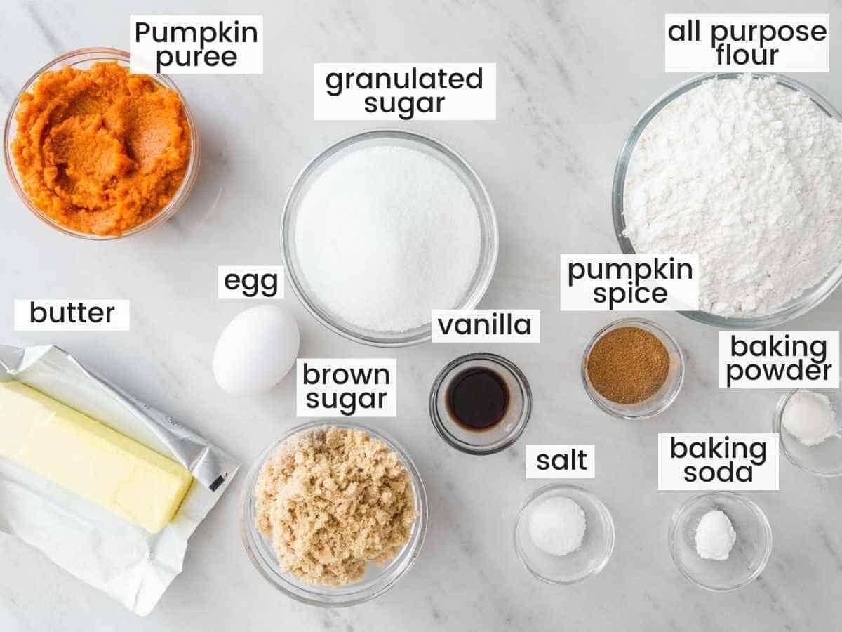 Ingredients needed to make pumpkin cookies including pumpkin puree, flour, sugar, butter, brown sugar, egg, vanilla, pumpkin spice, baking powder and soda, and salt.