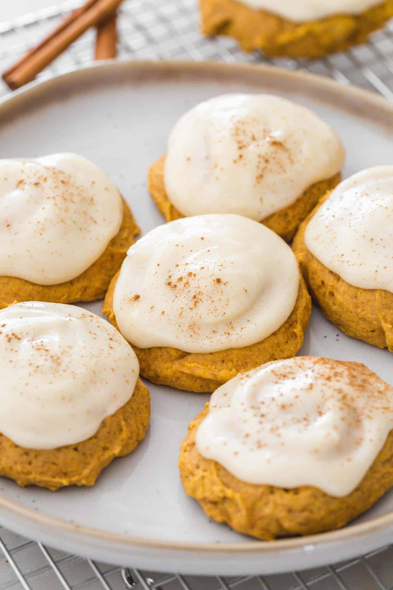 Pumpkin cookies frosted with cream cheese frosting served on a white plate, placed on a wire rack