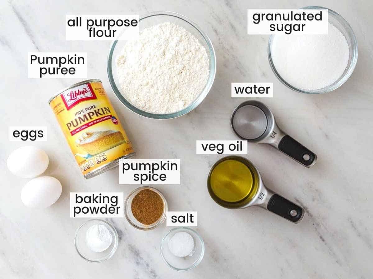 Ingredients needed to make pumpkin muffins including pumpkin puree, flour, eggs, oil, water, sugar, pumpkin spice, baking powder and salt.