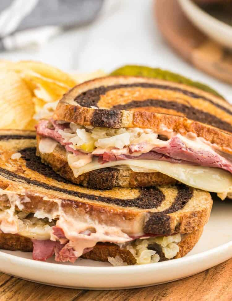 Two Reuben Sandwiches with Russian Dressing served on a white plate with potato chips