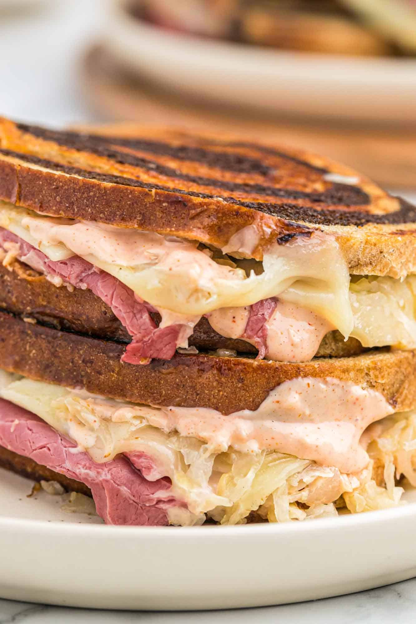 Stacked Reuben sandwiches served on a white plate