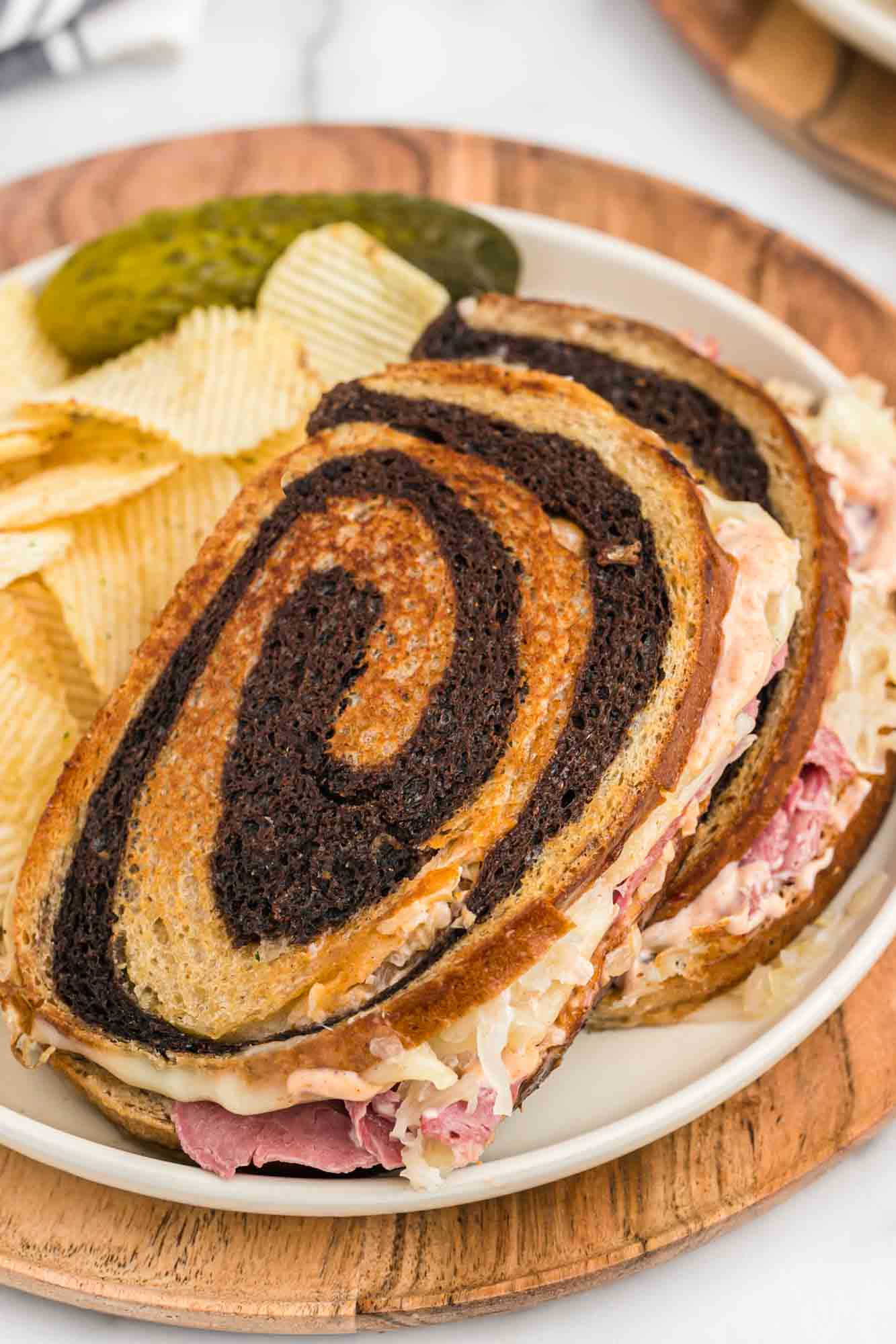 Overhead shot of reuben sandwiches made with marbled rye bread served on a white plate with potato chips and pickle spears