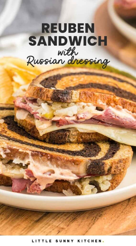 """Two Reuben Sandwiches with Russian Dressing served on a white plate with potato chips and overlay text that reads """"Reeuben"""