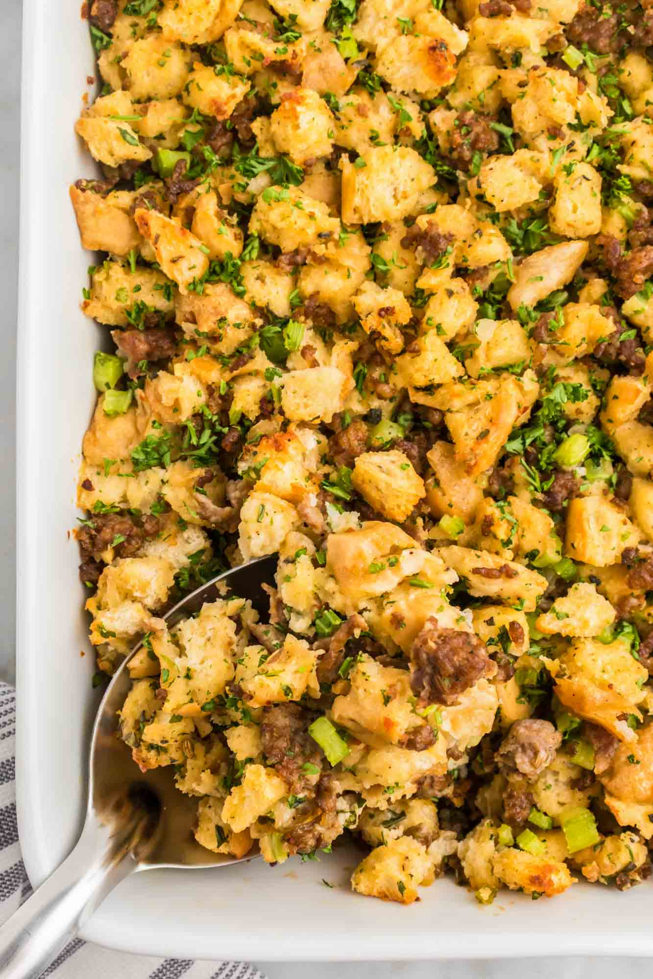 Overhead shot of sausage stuffing in a baking dish with a serving spoon