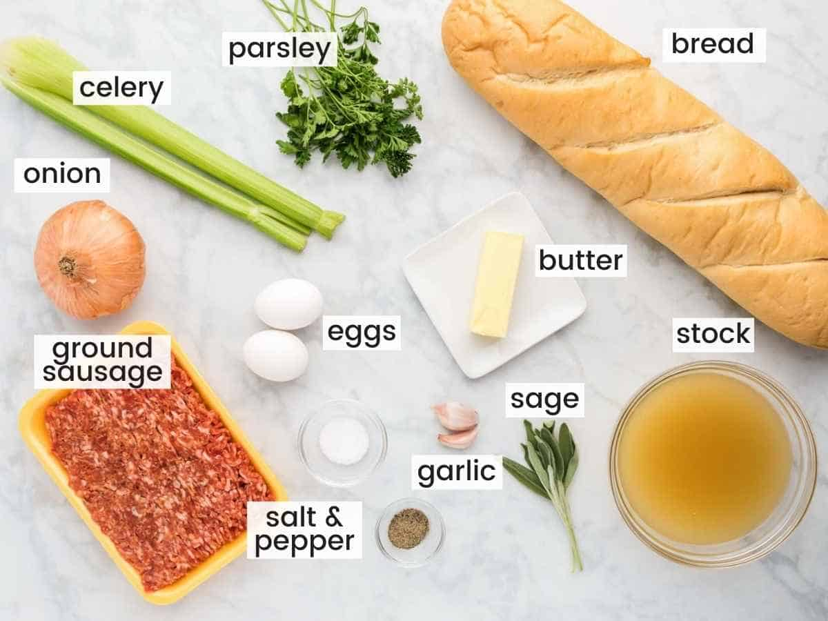 Ingredients needed to make sausage stuffing including bread, sausage, celery, onion, garlic, parsley, stock, eggs, sage and butter.