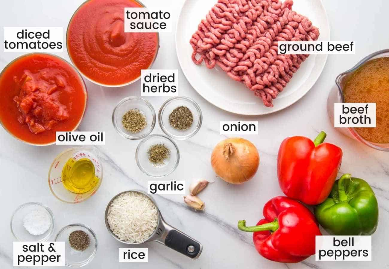 Ingredients needed to make stuffed pepper soup including bell peppers, ground beef, tomato, onion, garlic, rice, oil, broth, and seasonings.