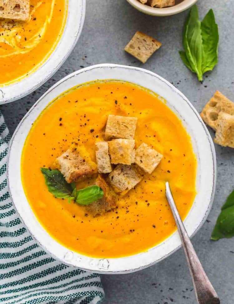 Overhead shot of 2 bowls of carrot soup with croutons