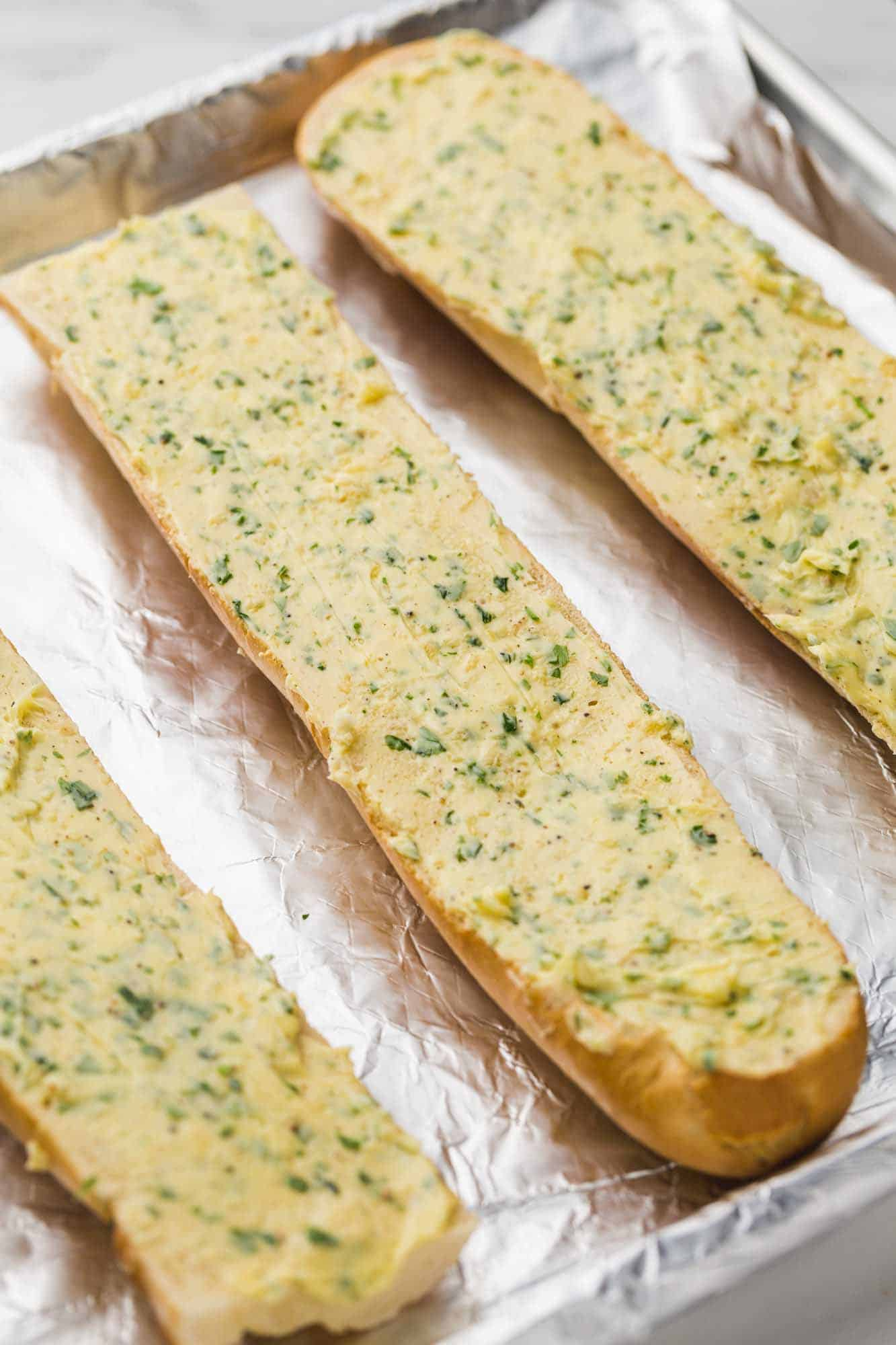 Garlic bread with the garlic spread before baking, placed on a foil lined baking sheet.