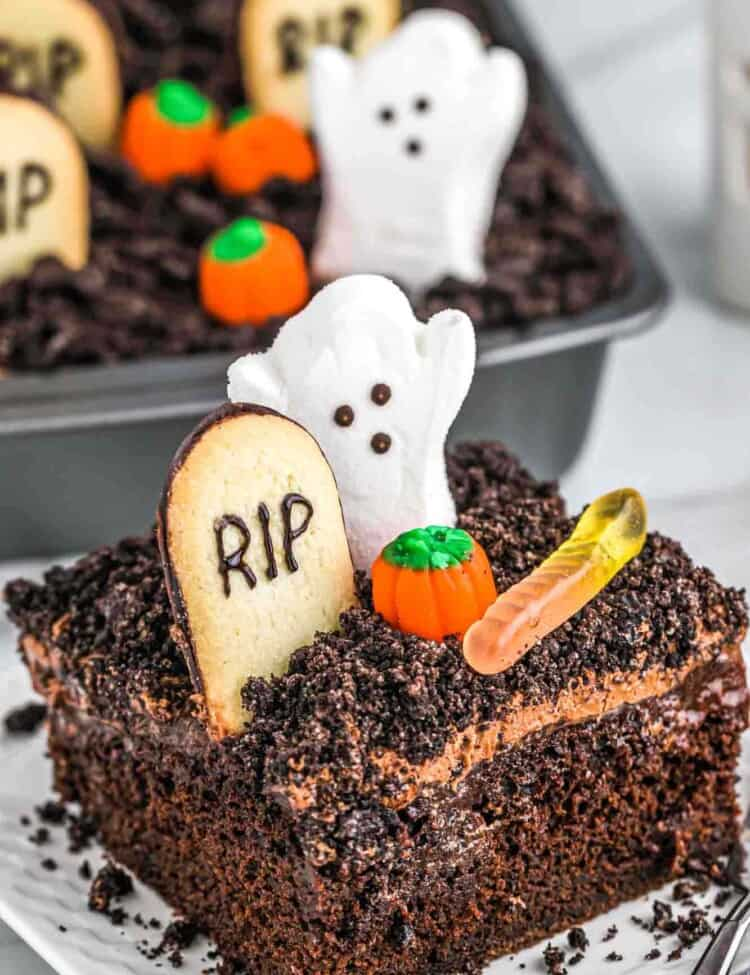 A slice of halloween dirt cake served on a square white plate