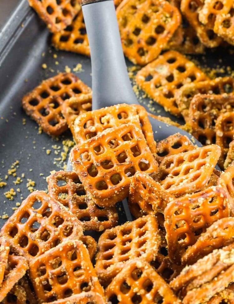 Honey mustard pretzels on a simmer sheet pan with a serving spoon