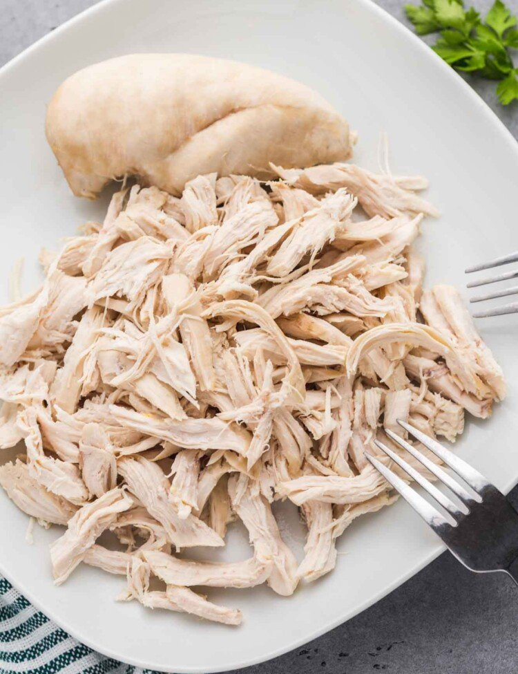 Shredded chicken breast on a white square plate with 2 forks