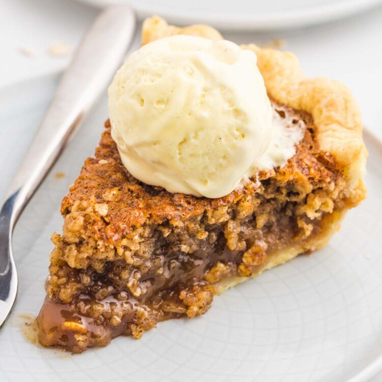 A slice of oatmeal pie served on a small white plate with a fork, topped with a scoop of vanilla ice cream