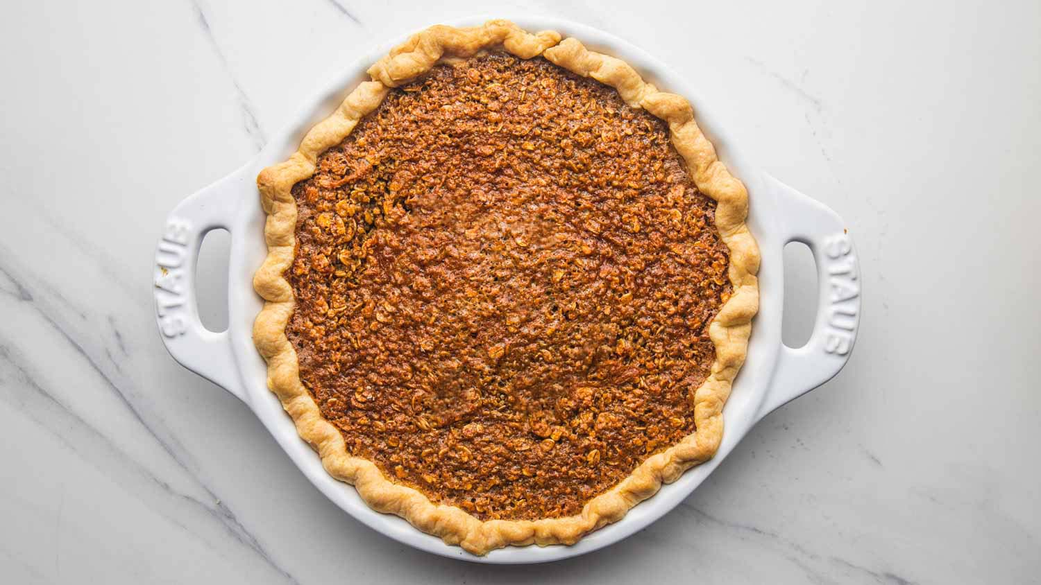 Overhead shot of baked oatmeal pie in a white Staub pie dish