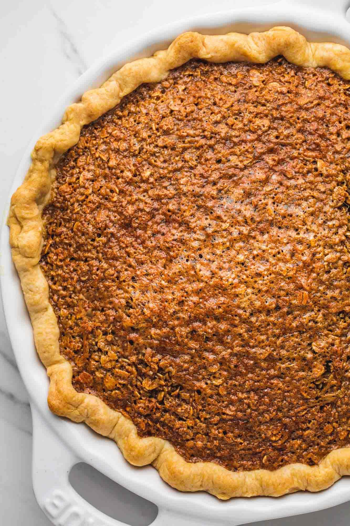 Overhead shot of oatmeal pie in a white Staub pie dish