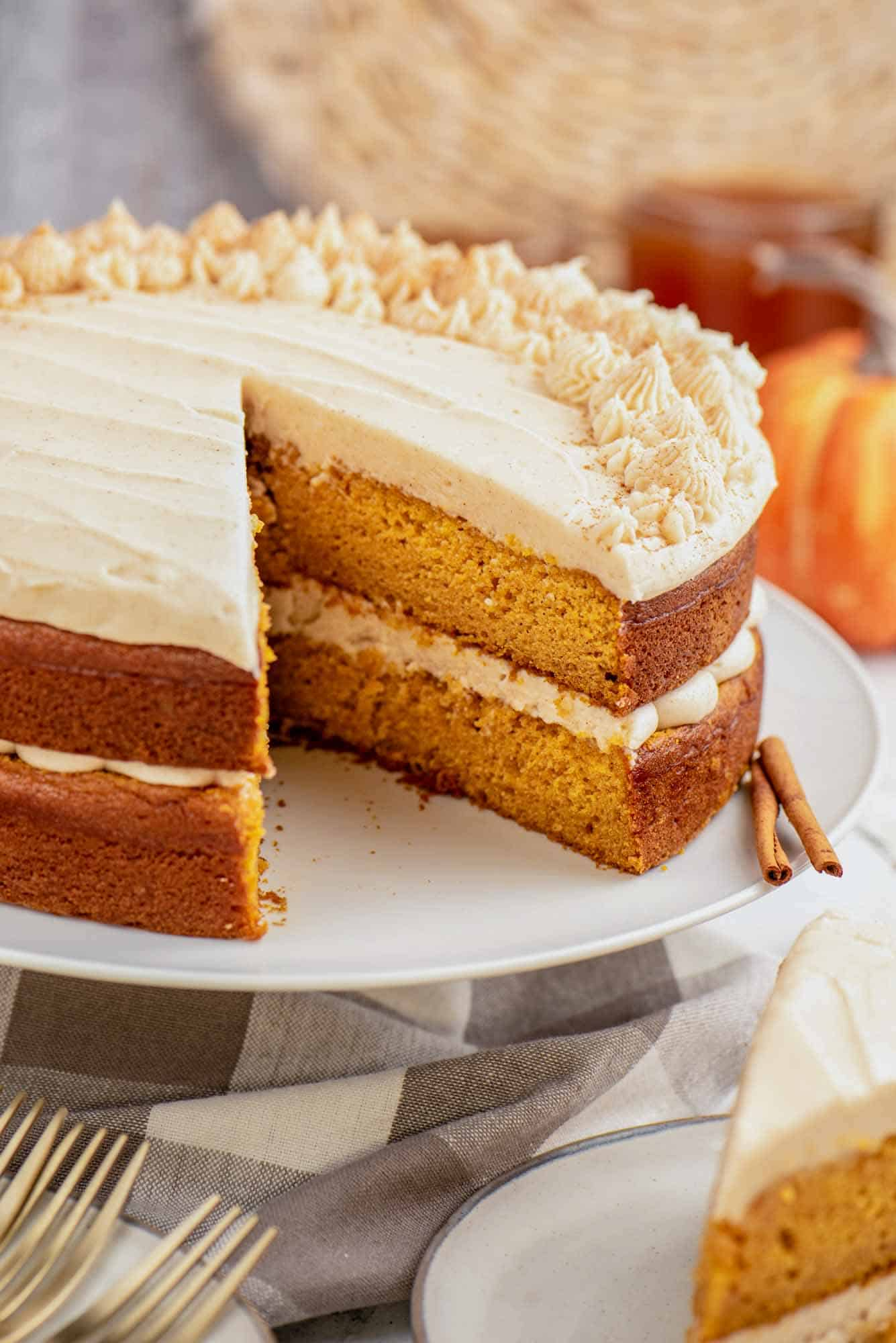 Pumpkin layer cake on a cake stand, frosted with cream cheese frosting