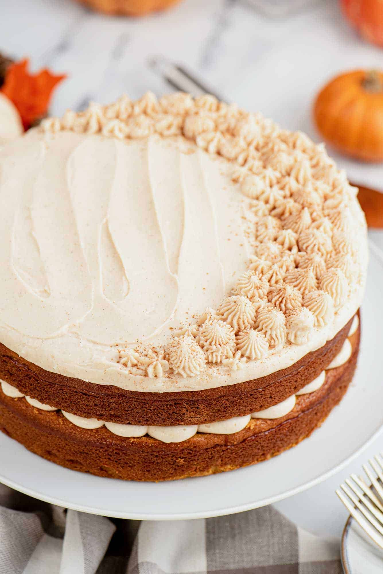 Frosted pumpkin cake on a white cake stand