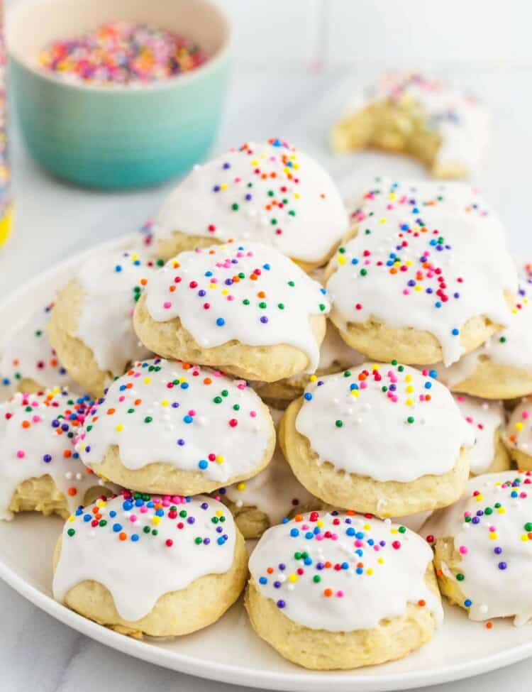Ricotta cookies are stacked on a white plate, and decorated with white glaze and colorful sprinkles.