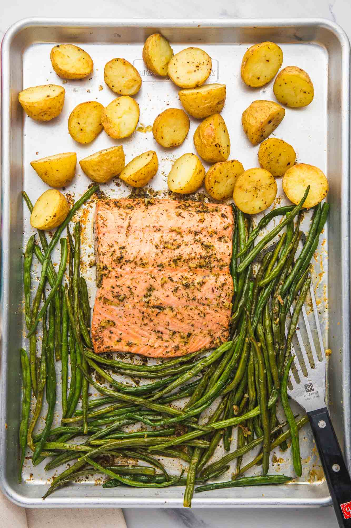 Overhead shot of sheet pan salmon with baby potatoes, green beans, and a fish spatula on the side.