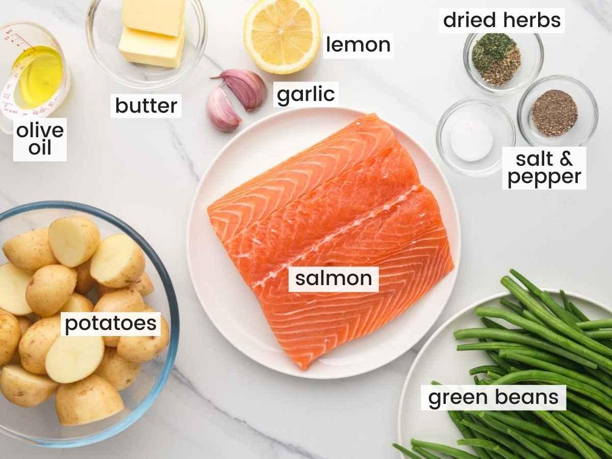 Ingredients needed to make sheet pan salmon including salmon fillet, potatoes, green beans, garlic, butter, lemon, and seasonings.