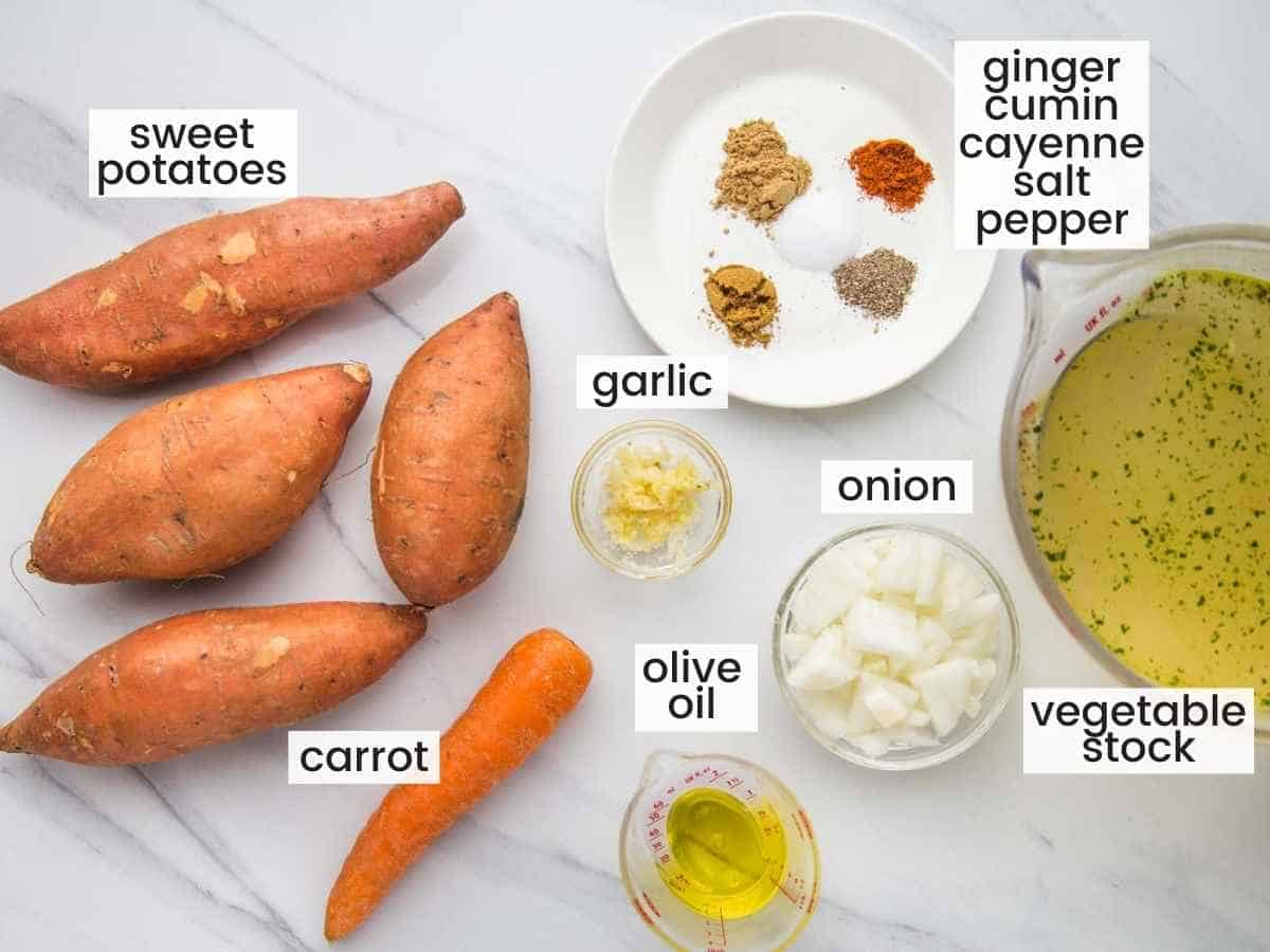 Ingredients needed to make sweet potato soup including sweet potatoes, onion, garlic, vegetable stock, olive oil, carrot, and seasonings.
