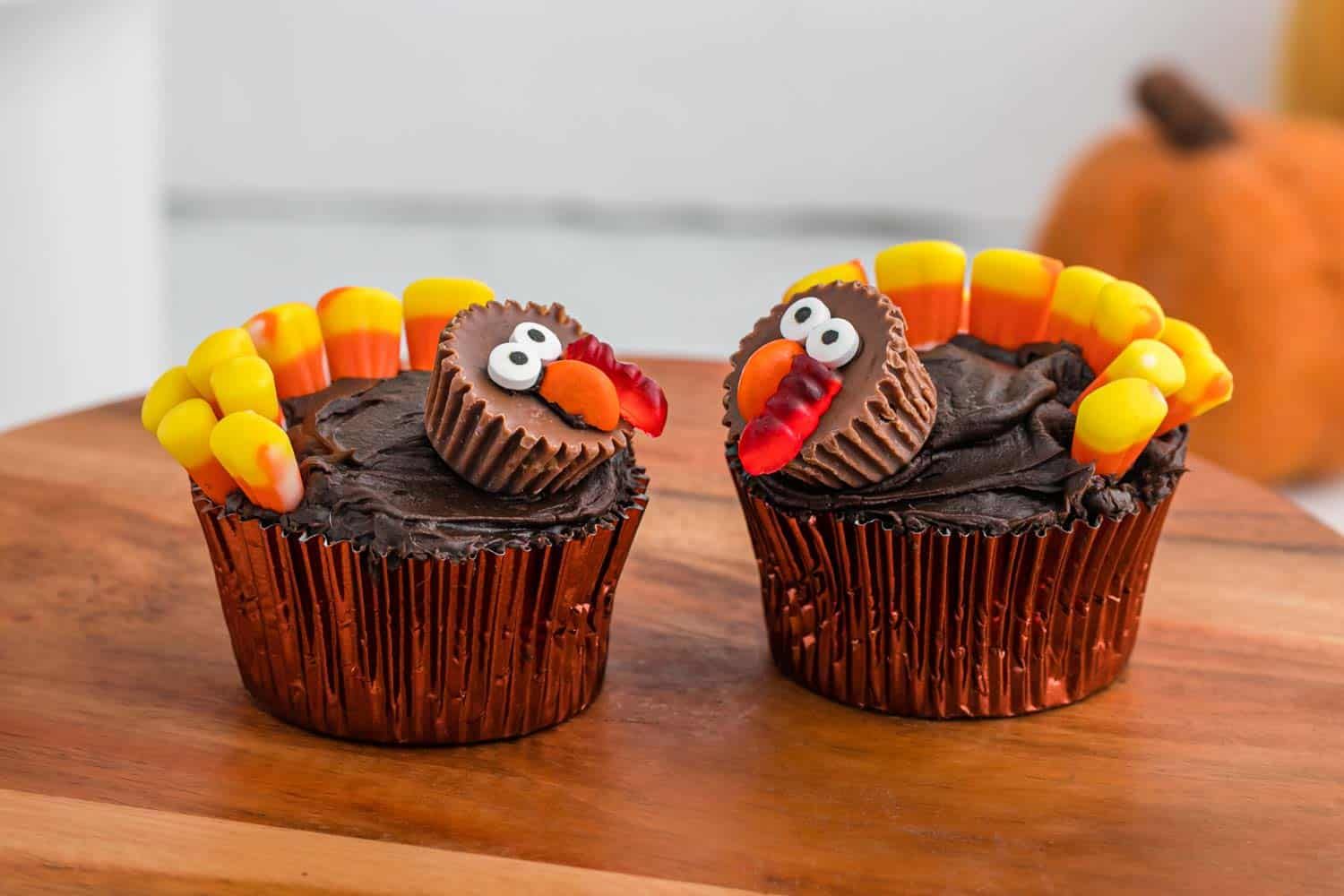 2 turkey cupcakes on a wooden tray
