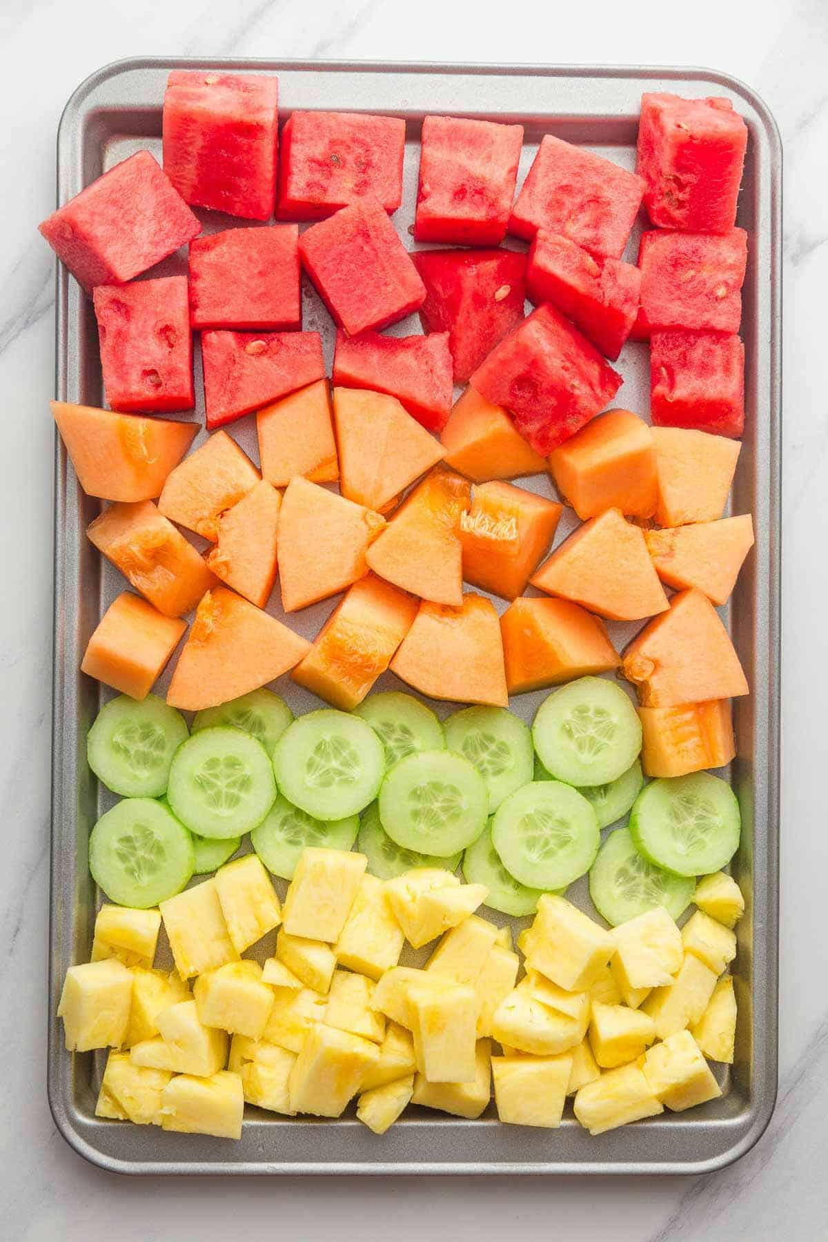 Chopped up fruit on a tray, watermelon, melon, cucumber, and pineapple.