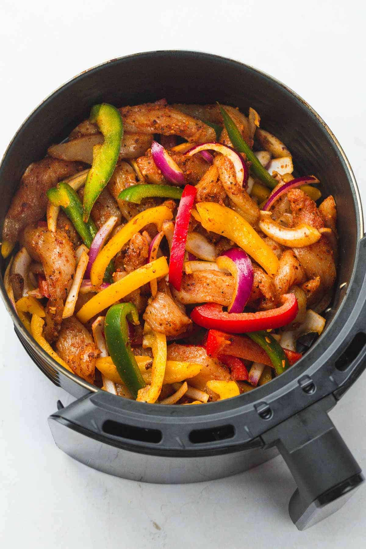 Raw chicken fajita strips and bell peppers in an air fryer basket.