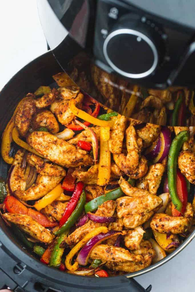 Chicken fajita strips and bell peppers in an air fryer basket