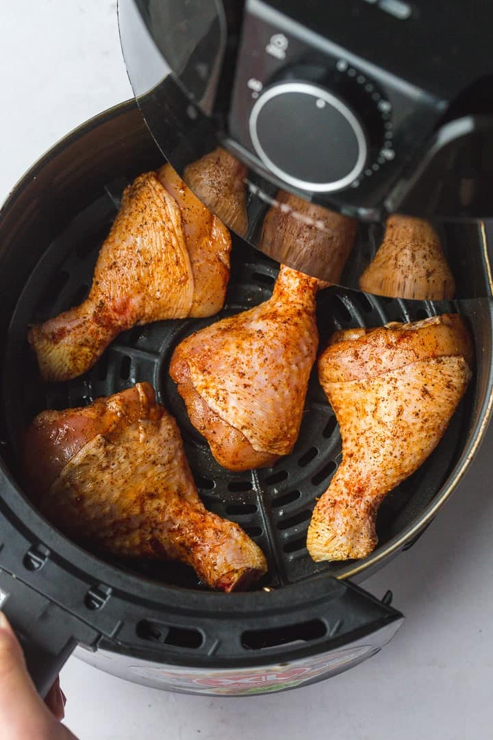 Placing the seasoned drumsticks in an air fryer basket.